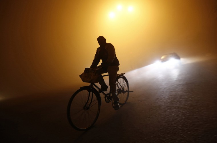 A man rides a bicycle through a road amid dense fog on a cold winter night in New Delhi January 5, 2014. Delhi is experiencing a dense fog, severely disrupting air, road and rail traffic in the national capital as cold wave conditions continue across most parts of north India with temperatures at most places remaining below normal, local media reported. Picture taken January 5, 2014. (Adnan Abidi/Reuters)