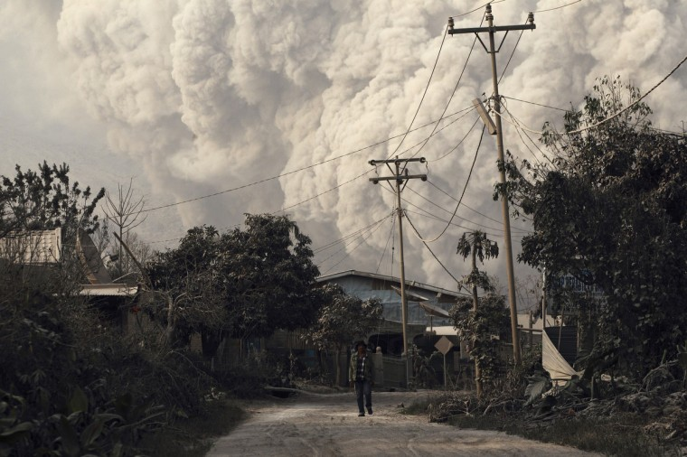 A villager walks as Mount Sinabung erupts at Beras Tepu village in Karo district, Indonesia's North Sumatra province. More than 25,000 villagers have been evacuated since authorities raised the alert status for the volcano to the highest level in November 2013, local media reported on Monday. (Beawiharta/Reuters)