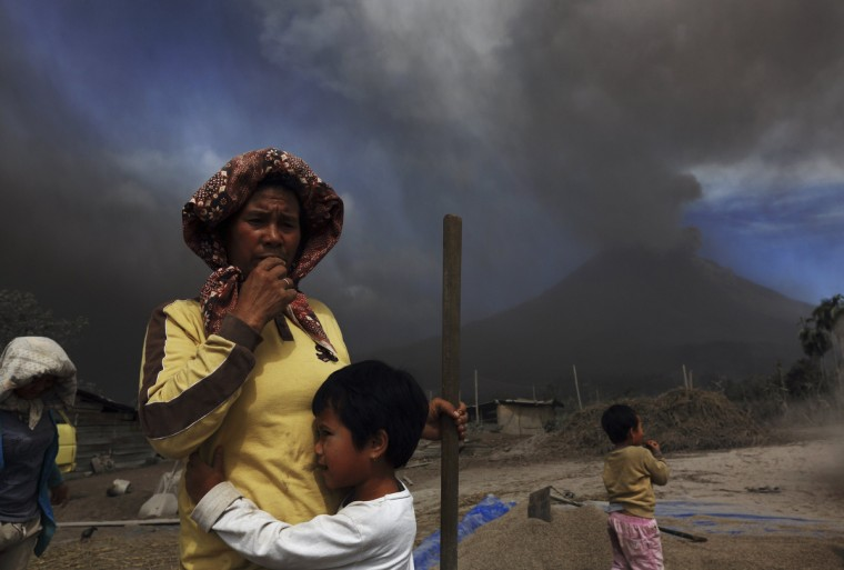 A child holds her mother next to piles of paddy seeds as ash and smoke fill the air during an eruption in Mount Sinabung (background R), at Tiga Pancur village in Karo district, Indonesia's North Sumatra province. More than 25,000 villagers have been evacuated since authorities raised the alert status for the volcano to the highest level in November 2013, local media reported on Monday. (Beawiharta/Reuters)