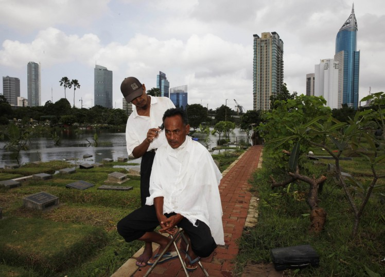 Cemetery worker Mohammad Udin has his hair cut by a mobile barber as the flooded cemetery complex is pictured in the background in Jakarta. Torrential rains that have continued in Jakarta in recent days widened the number of flooded areas to more than 10,000 affected houses, displacing close to 64,000 people. The death toll in Jakarta's rainy season has risen to 23, according to local media citing the Jakarta Disaster Mitigation Agency (BPBD) on Sunday. (Beawiharta/Reuters)