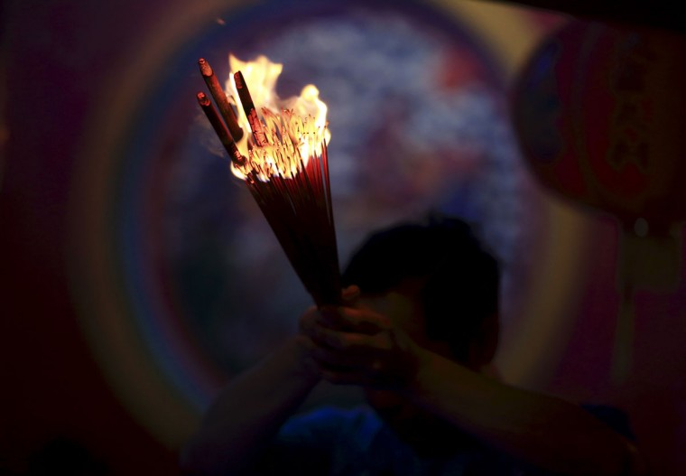A man prays for good fortune while holding incense on the first day of the Chinese Lunar New Year at Petak Sembilan Temple in Jakarta January 31, 2014. According to the Chinese lunar calendar, the Chinese New Year, which welcomes the year of the horse, falls on January 31. (REUTERS/Beawiharta)