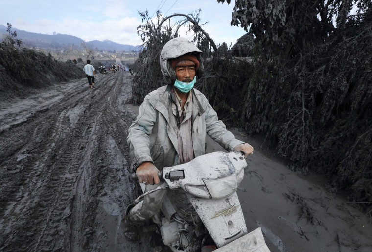 A villager rides his motorcycle through mud and ash spewed from Mount Sinabung as he evacuates to safety at Bekerah village in Karo district, Indonesia's North Sumatra province, January 11, 2014. More than 22,000 villagers have been evacuated since authorities raised the alert status for the volcano to the highest level in November 2013, local media reported on Friday. 9REUTERS/Beawiharta)