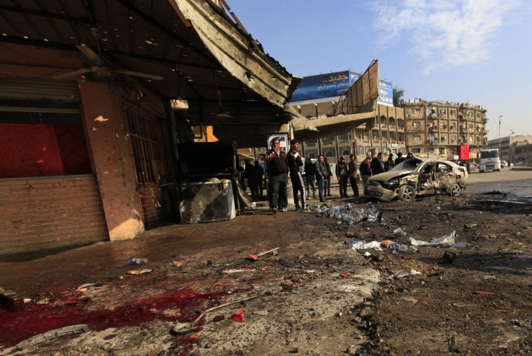 People gather at the site of a car bomb attack in Baghdad. Bomb attacks hit the Iraqi capital Baghdad and a village near the northern town of Baquba on Wednesday, killing at least 52 people, police and hospital sources said. (Ahmed Saad/Reuters)