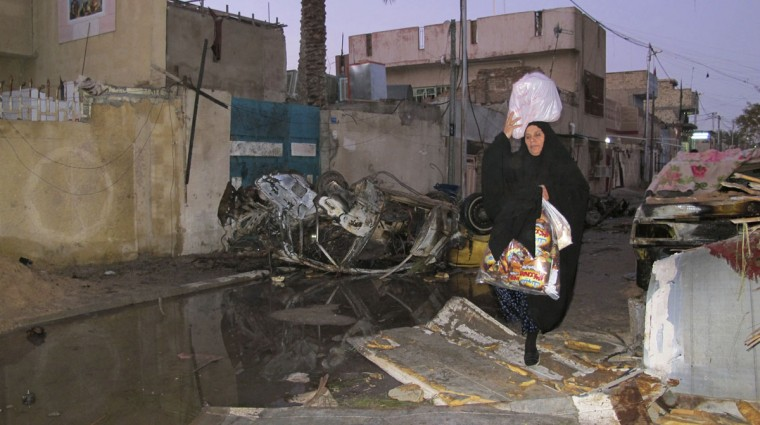 A woman walks past near the site of a bomb attack in Baghdad, January 30, 2014. Car bombs in mainly Shi'ite districts of the Iraqi capital and a shooting killed at least 19 people on Wednesday, police said, driving the death toll so far this month to nearly 1,000, according to Iraq Body Count. REUTERS/Ahmed Malik