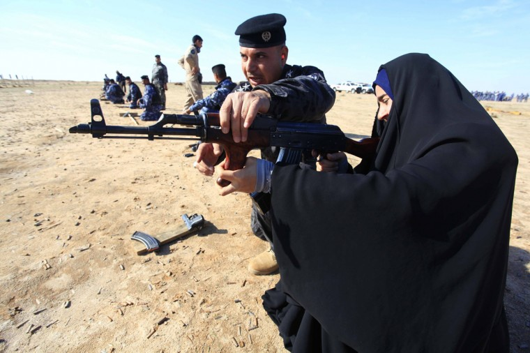 A female police trainee practises firing her weapon at a shooting range during a refresher training programme in Najaf January 20, 2014. Picture taken January 20, 2014. (Alaa Al-Marjani/Reuters)