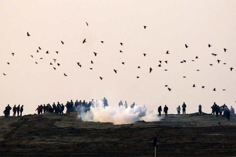 Palestinian demonstrators protest near the Israeli border fence with Gaza as the Israeli army shoots tear gas, January 3, 2014. (REUTERS/Amir Cohen)