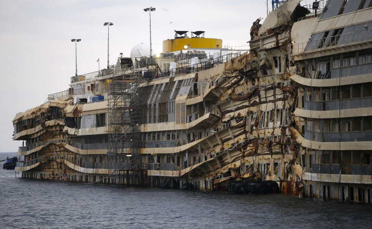 """The cruise liner Costa Concordia is seen during the """"parbuckling"""" operation outside Giglio harbour January 11, 2014. Thirty massive tanks filled with air will lift the hulk of the Costa Concordia off the seabed in June so it can be towed away from the Italian island of Giglio where it capsized two years ago, officials said on Friday. The 114,500-tonne vessel hit rocks on Jan. 13, 2012, killing 32 people. It was hauled upright in a complex """"parbuckling"""" operation in September but still rests where it capsized, just outside the holiday island's small port. Refloating the Concordia will be one more phase in the largest maritime salvage in history. Where the ship will be dismantled - the final step - has yet to be decided. (REUTERS/Max Rossi)"""
