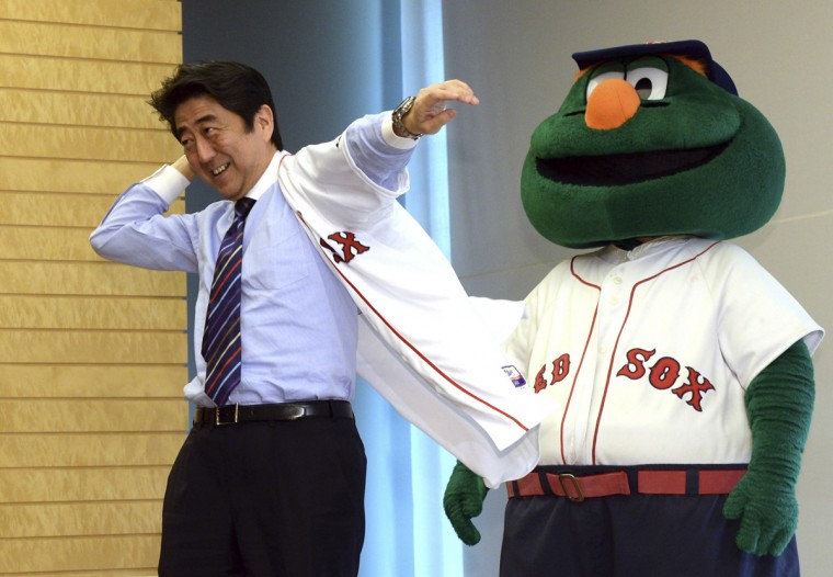 Japan's Prime Minister Shinzo Abe (L) smiles as he wears a jersey of Boston Red Sox, while Red Sox mascot Wally looks on at Abe's office in Tokyo January 21, 2014. Japanese Major League Baseball (MLB) players, Junichi Tazawa and Koji Uehara gave a Red Sox jersey to Abe. (Yoshikazu Tsuno/Pool/Reuters)
