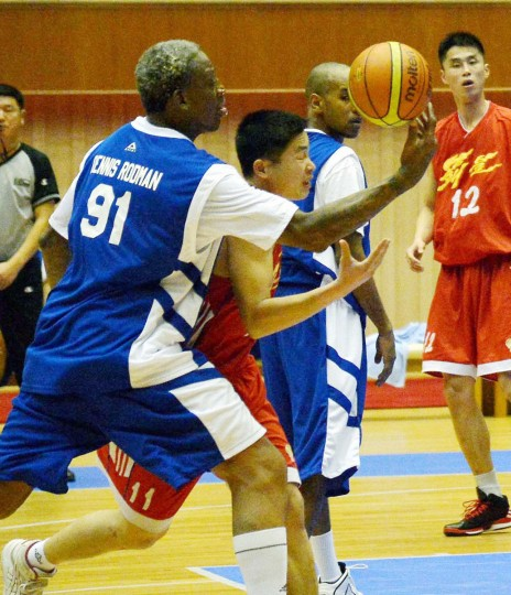 "Former NBA basketball star Dennis Rodman (L) fights for the ball during an international exhibition basketball match between the U.S. and North Korea in Pyongyang, in this photo released by Kyodo. Rodman led an auditorium of North Koreans in singing ""Happy Birthday"" to their leader on Wednesday, a day after the former U.S. basketball star sparked controversy by appearing to suggest a Korean-American was to blame for his captivity in North Korea. Mandatory credit (Reuters)"