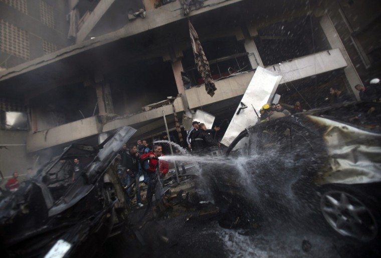 People attempt to extinguish a fire at the site of an explosion in Beirut's southern suburbs January 2, 2014. The powerful explosion in Shi'ite group Hezbollah's southern Beirut stronghold killed three people on Thursday and sent a column of smoke into the sky, a witness said. (REUTERS/Khalil Hassan)