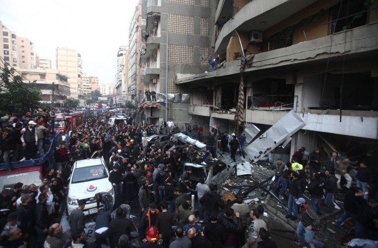 People gather at the site of an explosion in Beirut's southern suburbs, January 2, 2014. The powerful explosion in Shi'ite group Hezbollah's southern Beirut stronghold killed three people on Thursday and sent a column of smoke into the sky, a witness said. (REUTERS/Khalil Hassan)