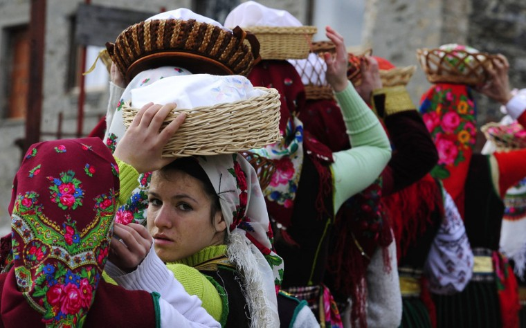 Villagers dressed in traditional folk costumes take part in an Epiphany celebration in Bitushe village, about 150 kilometers west of the capital Skopje, January 19, 2014. Bitushe practices a different Epiphany tradition: Instead of jumping into the water to retrieve a cross thrown by a priest, the village's women carry homemade bread on their heads while dressed in folk costumes to mark the welfare and health of their families. Women usually take part in the procession as most of the men are working abroad. (Ognen Teofilovski/Reuters)