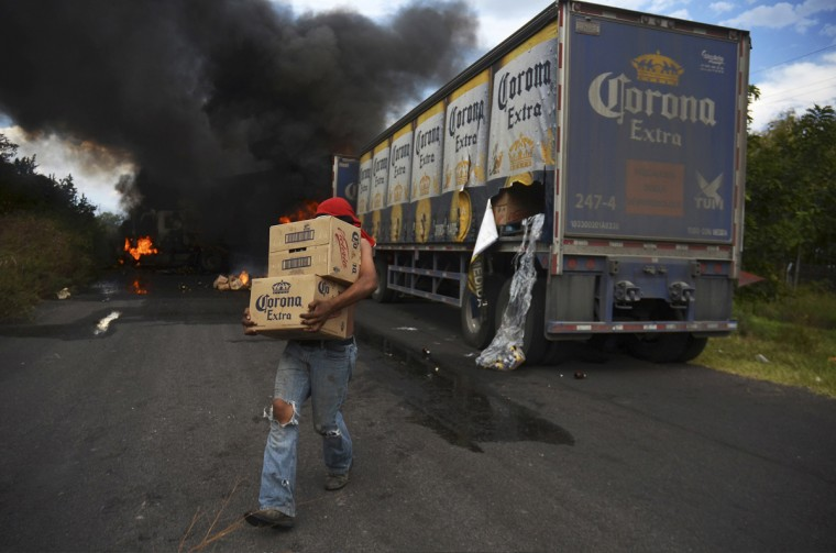 A looter carries boxes of beer as Corona truck burns in a road block allegedly set up by followers of the Knights Templar cartel in Tierra Caliente January 10, 2014. Mexico's government on Monday pledged to take control of a violent western state after days of fighting between masked vigilantes and members of one of the country's most powerful drug cartels. Since late last year, vigilante groups in the state of Michoacan have moved deeper into territory controlled by the Knights Templar cartel and they now are converging on Apatzingan, considered one of gang's main strongholds. Picture taken January 10, 2014. (Alan Ortega/Reuters)