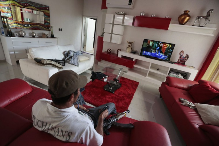 "Vigilante ""El Love"" channel-surfs on a plasma TV while sitting in the living room of the house of a top leader of the Caballeros Templarios, or Knights Templar, in Nueva Italia January 16, 2014. The drug lord and his family left the house as they fled an uprising led by farmers exasperated with organized crime. The Knights Templar have openly defied the government, putting out videos in the media and accusing the vigilantes of being infiltrated by other criminal gangs moving into Michoacan. Vigilantes who claim to number in the thousands have taken the fight to organized crime and put the Caballeros on the run. REUTERS/Jorge Dan Lopez"