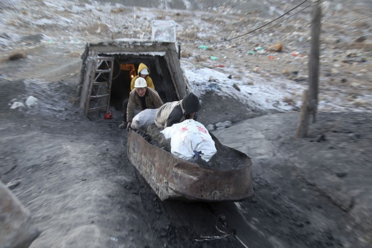 Workers push a cart carrying coal out of a shaft at a coal mine at Nalaikh, southeast of Ulan Bator January 24, 2014. According to local media, over the past decade many miners were killed in accidents in Nalaikh due to the backward working conditions. Picture taken January 24, 2014. (REUTERS/B.Rentsendor)