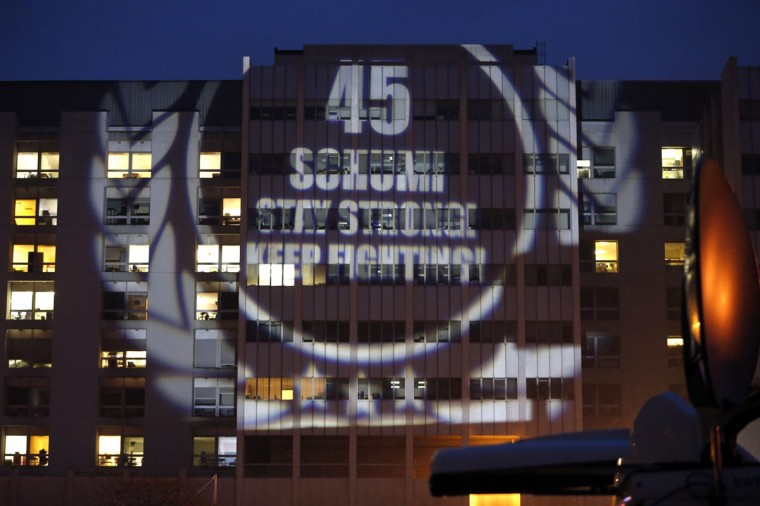 """A message to mark the 45th birthday of seven-time Formula One world champion Michael Schumacher is projected by fans on the facade of the CHU hospital emergency unit in Grenoble, French Alps, where Schumacher is hospitalized January 3, 2014. His agent said on Wednesday that Schumacher was in a stable condition and it was too early to talk about his further prospects. No further update was given on Thursday, the day before his 45th birthday. Schumacher is battling for his life after slamming his head against a rock while skiing off-piste in the French resort of Meribel on Sunday. The message reads """"45, Schumi, stay strong, keep fighting"""". (REUTERS/Charles Platiau)"""