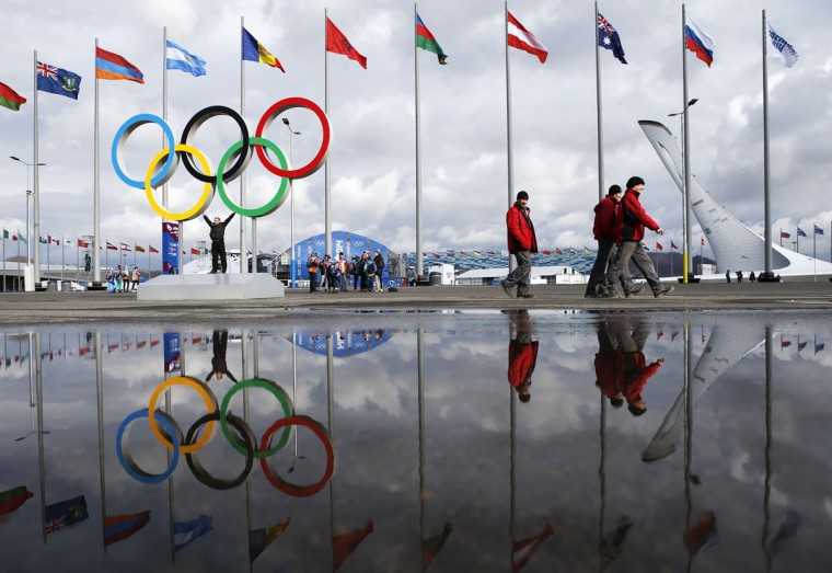 People walk past as the Olympic rings and the cauldron for the Olympic flame are reflected in a puddle of water on the Olympic Park as preparations continue for the Sochi 2014 Winter Olympics January 30, 2014. The opening ceremony for the winter games will be held February 7. REUTERS/Fabrizio Bensch
