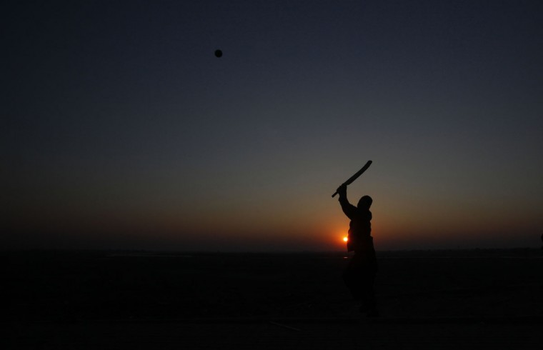 A man is silhouetted against the setting sun as he plays cricket at a park in Lahore on January 3, 2014. (REUTERS/Mohsin Raza)
