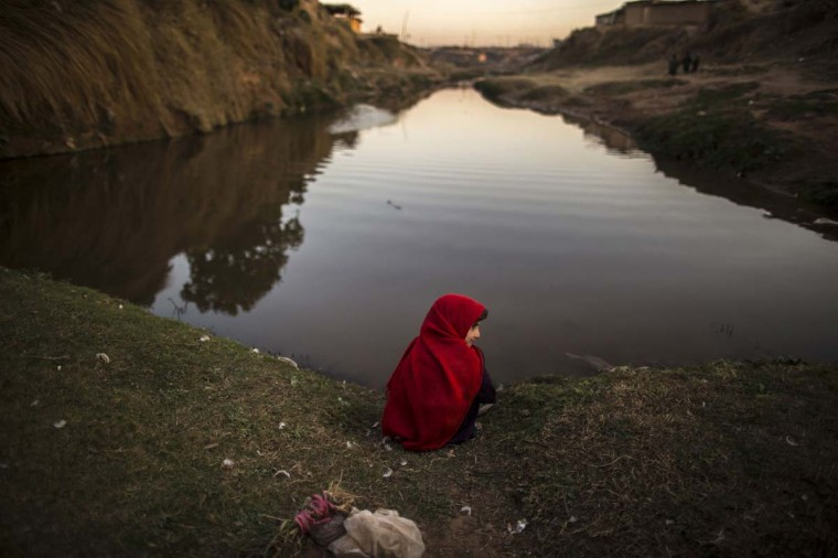 A girl sits at the edge of a stream in a slum on the outskirts of Islamabad January 27, 2014. (Zohra Bensemra/Reuters)