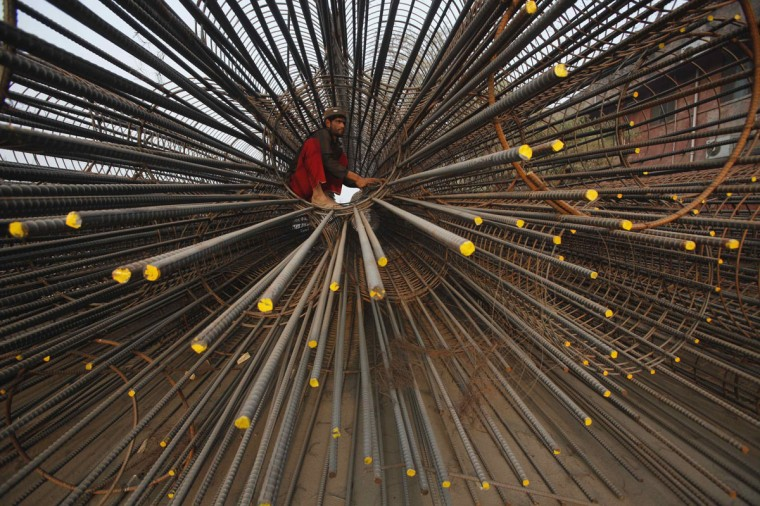A labourer works on the scaffoldings of a flyover under construction in Lahore January 31, 2014. (REUTERS/Mohsin Raza)