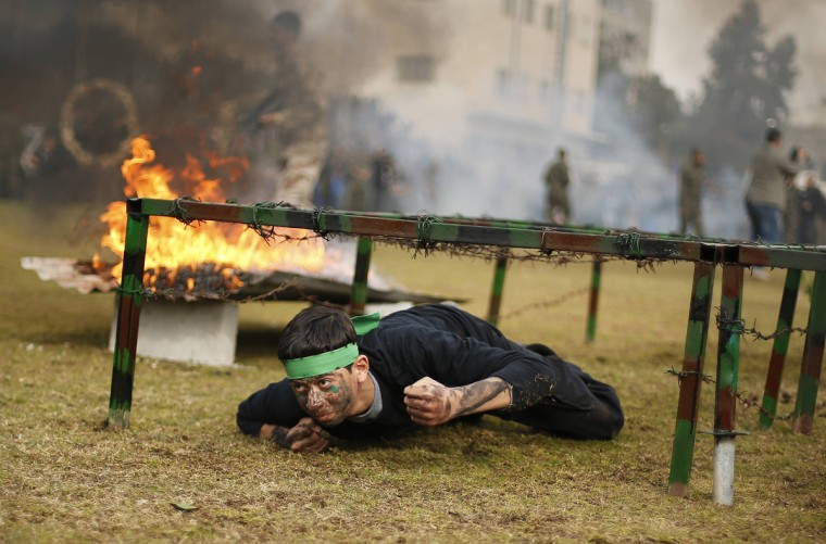 """A Palestinian student crawls under a barbed wire obstacle next to a fire during a graduation ceremony for a military-style training programme in Gaza City January 14, 2014. Some 13,000 students joined the course, which is aimed at preparing them for """"liberating Palestine from Israel"""", Hamas officials said. The course was conducted by the Hamas-run ministry of education during the school winter holiday. (Suhaib Salem/Reuters)"""