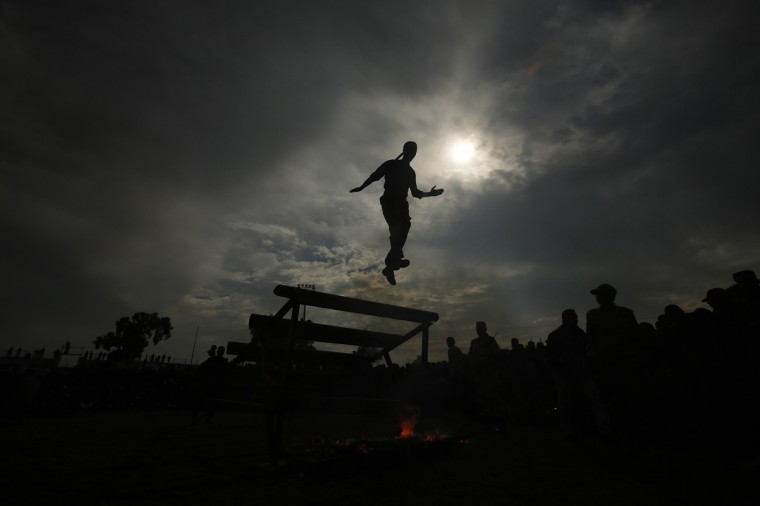 "A Palestinian student jumps from the top of an obstacle during a graduation ceremony for a military-style training programme in Gaza City January 14, 2014. Some 13,000 students joined the course, which is aimed at preparing them for ""liberating Palestine from Israel"", Hamas officials said. The course was conducted by the Hamas-run ministry of education during the school winter holiday. (Suhaib Salem/Reuters)"
