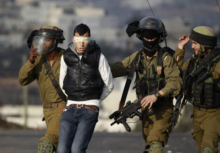 Israeli soldiers arrest a Palestinian during clashes with Israeli troops at a protest against the Jewish settlement of Ofra, in the West Bank village of Silwad, near Ramallah January 17, 2014. REUTERS/Mohamad Torokman
