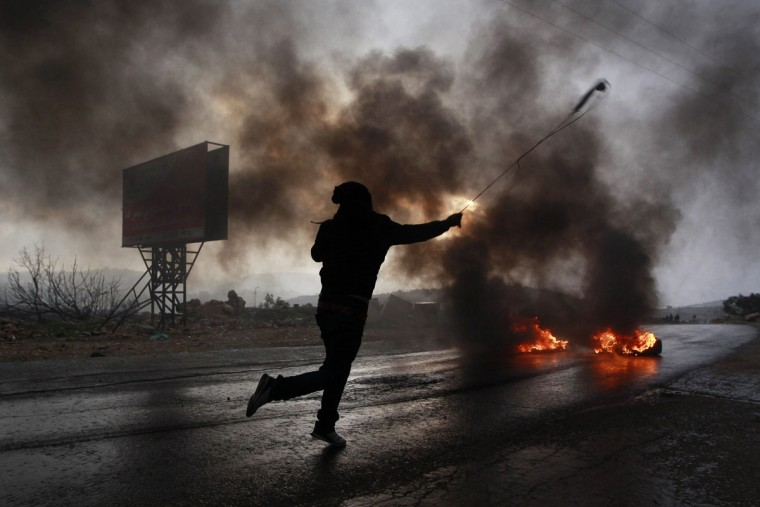 A Palestinian protester uses a sling to hurl a stone during clashes with Israeli troops at a protest against the Jewish settlement of Ofra, in the West Bank village of Silwad, near Ramallah January 10, 2014. Israel on Friday announced plans to build 1,400 new homes in the occupied West Bank and East Jerusalem, days after U.S. Secretary of State John Kerry visited the region to push peace talks in which settlements represent a major hurdle. (REUTERS/Mohamad Torokman)
