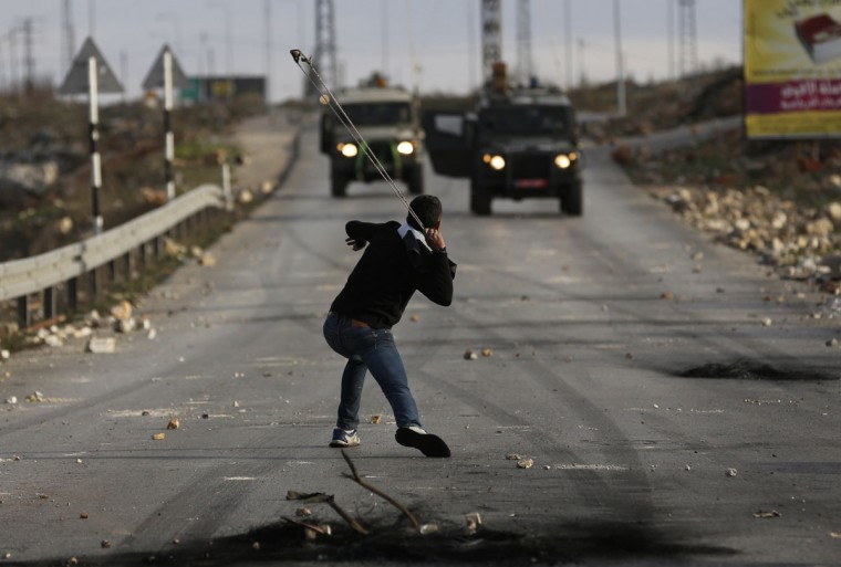 A Palestinian protester uses a sling to throw a stone during clashes with Israeli soldiers in Jalazoun refugee camp near the West Bank city of Ramallah January 31, 2014. Clashes broke on Friday between stone-throwing protesters and Israeli soldiers, two days after Muhammad Mubarak, 21, a resident of the refugee camp was killed by Israeli soldiers who said he had opened fire on their position near a Jewish settlement in the occupied West Bank. (REUTERS/Darren Whiteside)