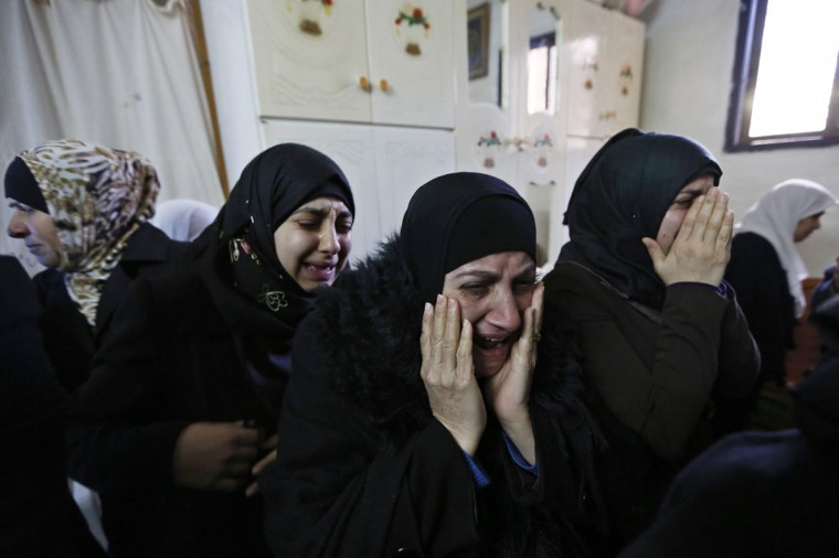 Relatives mourn before the funeral of Palestinian Saeed Jaser Ali, 85, in the West Bank village of Kufr Kadum near Nablus January 2, 2014. Ali died on Thursday after inhaling tear gas fired by the Israeli army to disperse protesters in the occupied West Bank, witnesses said. (REUTERS/Mohamad Torokman)