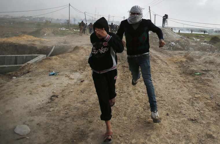 Palestinian protesters run after Israeli army fired tear gas canisters during clashes near the border between Israel and east Gaza Strip January 17, 2014. REUTERS/Suhaib Salem