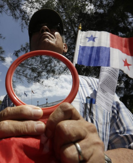 A man holds a mirror reflecting the Spanish flag during a protest outside the Spanish embassy in Panama City January 22, 2014. Demonstrators protested against the Spanish building company Sacyr, one of the leading members of the consortium to expand the Panama Canal. protesters used mirrors resembling how Spanish conquerors exchanged mirrors for gold to the Indians when they first arrived to America. (REUTERS/Carlos Jasso)