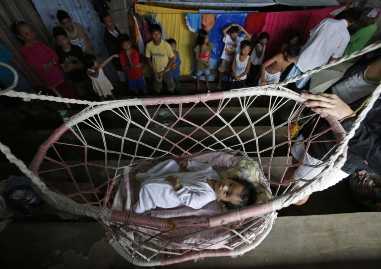 "A baby rests on a hammock inside an indoor basketball gym, which has been turned into an evacuation centre for flooding victims, in Jabonga, Agusan del Norte in southern Philippine island of Mindanao January 17, 2014. The death toll from the floods and landslides in Mindanao caused by a lingering low-pressure area climbed to 34 on Friday, while more than 300,000 people are displaced due to flooding and landslides, the National Disaster Risk Reduction and Management Council reported. Storm Signal No. 1 has been raised in seven provinces in Mindanao on Friday after a low pressure area in the area developed into a tropical depression now named ""Agaton"", the Philippine Atmospheric, Geophysical And Astronomical Services Administration (Pagasa) said. REUTERS/Erik De Castro"
