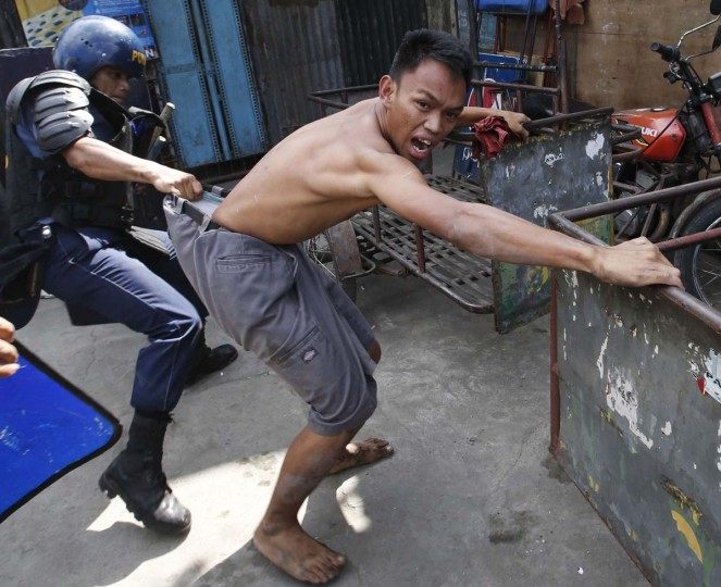A policeman detains a squatter dweller during clashes at a squatter district in Quezon city, Metro Manila January 27, 2014. Dozens were hurt during clashes triggered by the demolition of a squatter settlement for business developments in suburban Quezon city on Monday, local media reported. (Erik De Castro/Reuters)