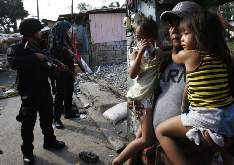 A squatter dweller carries his children as they leave their shanty house during the demolition of a squatter colony in Quezon city, Metro Manila January 27, 2014. Dozens were hurt during clashes triggered by the demolition of a squatter settlement for business developments in suburban Quezon city on Monday, local media reported. (Erik De Castro/Reuters)
