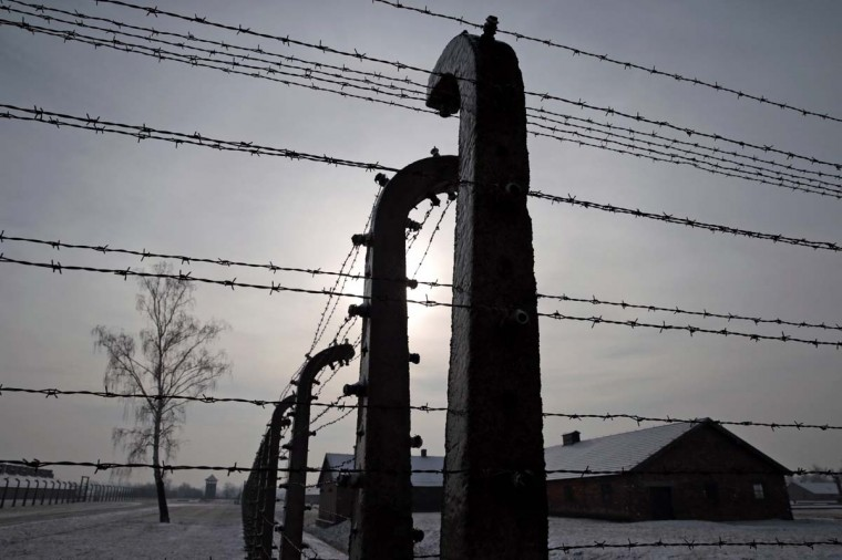 Former Auschwitz-Birkenau concentration camp is pictured through a barbed wire fence during ceremonies to mark the 69th anniversary of the liberation and commemorate the victims of the Holocaust in Birkenau January 27, 2014. The world marks International Holocaust Remembrance Day on January 27 to remember those who died during the Nazi organised genocide during World War Two that cost the lives of millions of Jews, Roma and Sinti, homosexuals and opponents to Germany's fascist regime and its collaborators. (Kacper Pempel/Reuters)