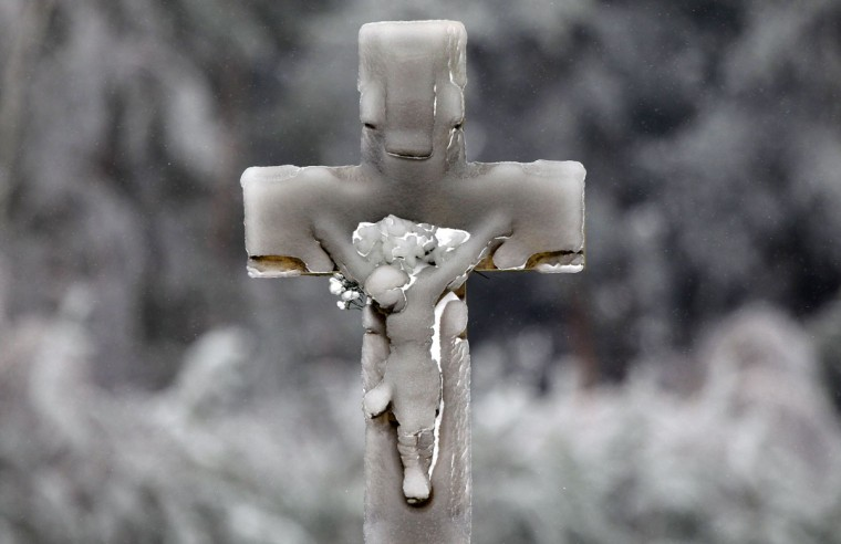 A cross is covered by icicle caused by frozen rain in Alojzow near Ilza, January 22, 2014. (REUTERS/Kacper Pempel)