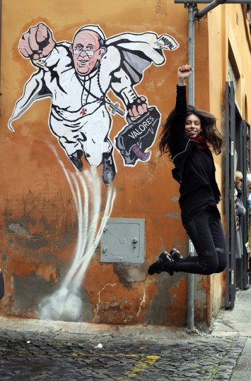 A woman jumps as a friend (not seen) takes a photo in front of a large drawing of Pope Francis depicting him as a superhero near the Vatican. The Argentinian Pope is shown taking off into air with his right fist clenched in a classic Superman style. (Alessandro Bianchi/Reuters)