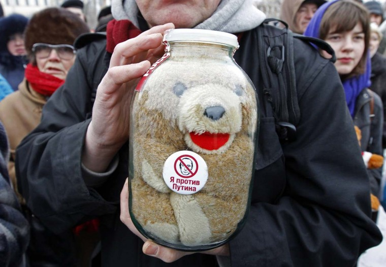 "People take part in a rally to protest against the law, passed in late December 2012, that bans Americans from adopting Russian children, with a toy seen inside a glass jar in the foreground, in St. Petersburg, January 13, 2013. Thousands of demonstrators gathered for a march in Moscow on Sunday to protest against a ban on Americans adopting Russian children, saying President Vladimir Putin's government had made orphans pawns in a political dispute. The sticker reads ""I'm against Putin"". (Reuters/Alexander Demianchuk)"