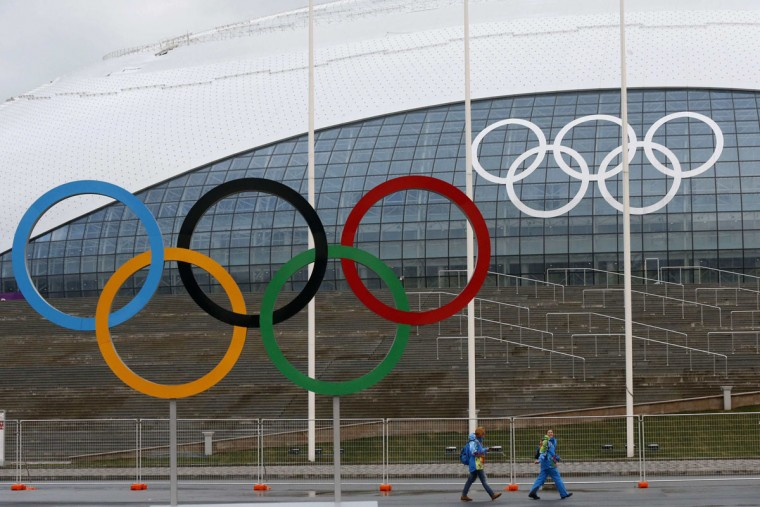 Volunteers walk along of the Olympic rings in front of the Bolshoy Ice Dome at the Olympic Park, in the Adler district of Sochi, January 24, 2014. Sochi will host the 2014 Winter Olympic Games from February 7 to 23. (REUTERS/Alexander Demianchuk)