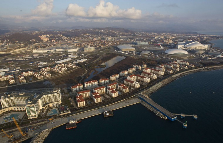 An aerial view from a helicopter shows the Olympic Park (R) under construction and the Olympic Village (C, bottom) in the Adler district of the Black Sea resort city of Sochi, December 23, 2013. Sochi will host the 2014 Winter Olympic Games in February. Picture taken December 23, 2013.