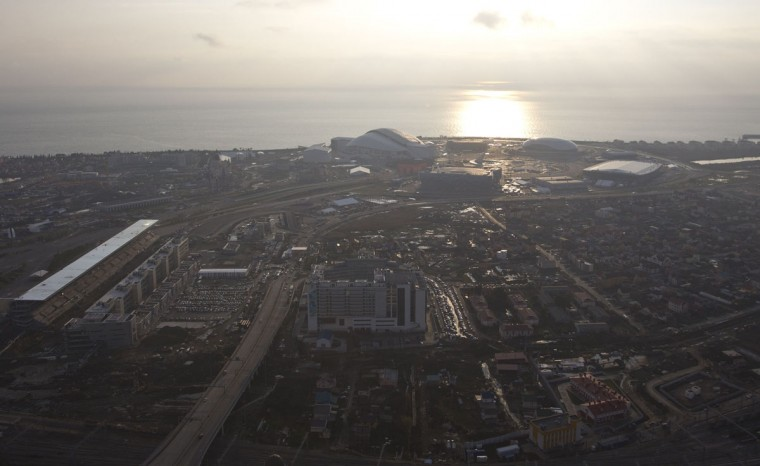 "An aerial view from a helicopter shows the Adler district, with the Olympic Park under construction seen in the background, in the Black Sea resort city of Sochi, December 23, 2013. Sochi will host the 2014 Winter Olympic Games in February. The view shows the ""Fisht"" Olympic Stadium (R) and the ""Iceberg"" Skating Palace (2nd L, top). Picture taken December 23, 2013."