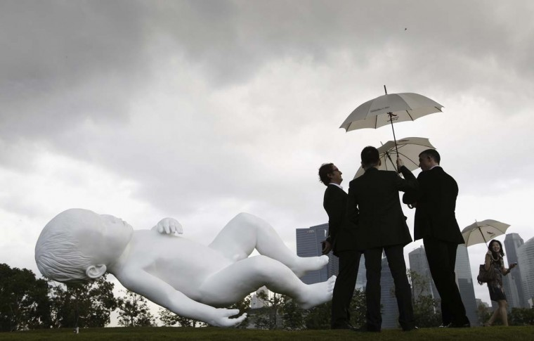 """Visitors carrying umbrellas look at the newly unveiled creation of British artist Marc Quinn, a 9m (30 feet) long painted bronze sculpture entitled """"Planet"""" at Gardens by the Bay in Singapore January 18, 2013. (Edgar Su/Reuters)"""