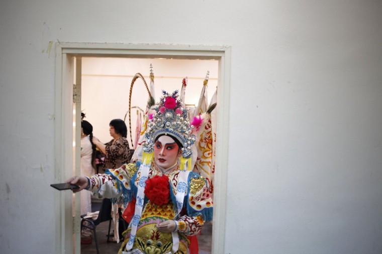 A performer passes his mobile phone to an assistant as they get ready for a Chinese opera performance for elderly guests invited by welfare organisations ahead of Lunar New Year in Singapore January 10, 2014. The opera show was organised by Shan You, a voluntary welfare organisation, which was raising funds to continue their services to the elderly. (REUTERS/Edgar Su)
