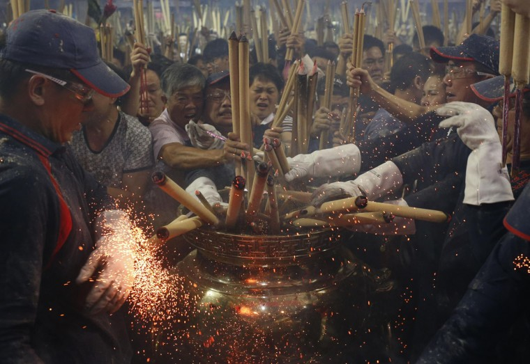 People rush to plant the first joss stick of the Chinese New Year at the stroke of midnight at a temple in Singapore early January 31, 2014. The Lunar New Year, which welcomes the year of the horse, falls on Friday. (REUTERS/Edgar Su)