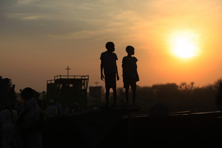 Children displaced by the fighting in Bor county, who have just arrived, are standing on the side of a boat in the port in Minkaman, in Awerial county, Lakes state, in South Sudan. (Andreea Campeanu/Reuters)