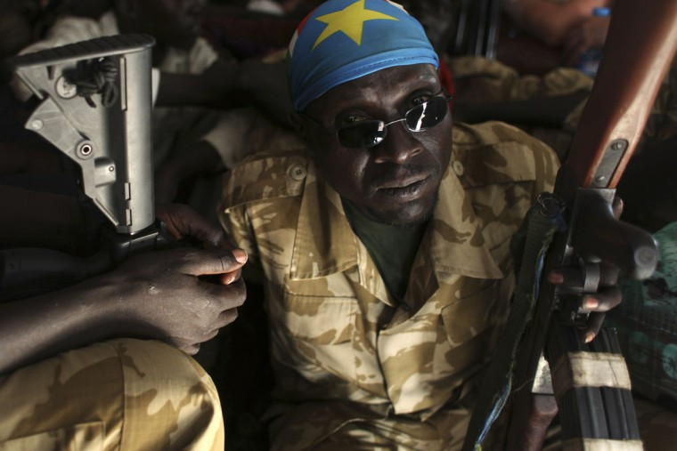A SPLA soldier sits on the floor of a helicopter during a trip from Bor to Juba, after visiting Bor, January 19, 2014. South Sudanese government forces said they seized the flashpoint town of Bor back from rebels on Saturday. (Andreea Campeanu/Reuters)