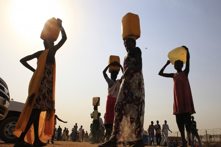 Displaced people carry water containers on their heads at Tomping camp, where some 15,000 displaced people who fled their homes are sheltered by the United Nations, near South Sudan's capital Juba January 7, 2014. (James Akena/Reuters)