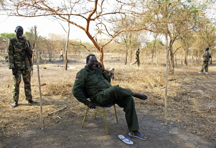 South Sudan's rebel leader Riek Machar sits in the bush as he talks on a phone to a Reuters journalist in a rebel-controlled territory in Jonglei State January 31, 2014. A regional African group mediating to end the conflict in South Sudan aims to deploy the first monitors of a shaky ceasefire at the weekend, senior officials said on Friday. The government of President Salva Kiir and rebels loyal to his sacked deputy Riek Machar agreed a ceasefire deal on January 23, but both sides have accused each other of violations. (REUTERS/Goran Tomasevic)