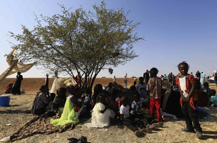 South Sudanese refugees wait at a border gate in Joda, in the Jableen locality in Sudan's White Nile State, after arriving from the South Sudanese war zones of Malakal and al-Rank, January 16, 2014. REUTERS/Mohamed Nureldin Abdallah